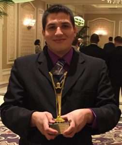MANUEL FELIX WITH THE GOLD STEVIE AWARD AT THE 2015 AWARDS BANQUET
